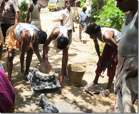 sculptors taking away mud from ganeshs pedestal